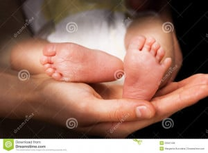 Royalty Free Stock Image: Moms hands holding baby s feet