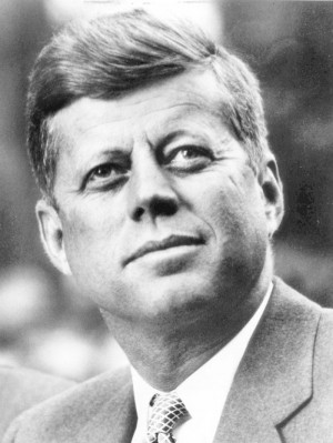 Black and white head and shoulders portrait of Kennedy looking up to ...