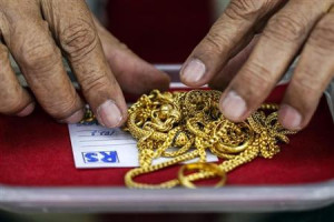 pawn shop worker sorts through gold jewellery at Easy Money Pawn ...