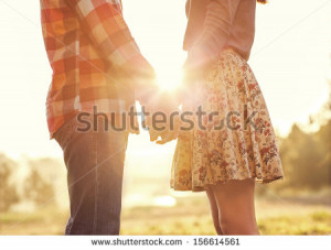 Young couple in love walking in the autumn park holding hands looking ...