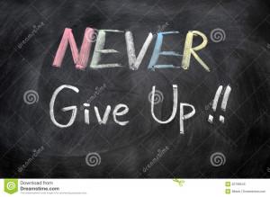 Never give up written in chalk on a blackboard.