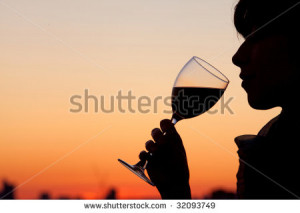 Woman drinking a glass of wine by the sunset - stock photo