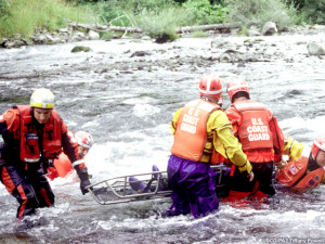 Coast Guard personnel rescuing an individual from a fast-flowing river ...