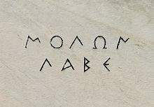 The words ΜΟΛΩΝ ΛΑΒΕ as they are inscribed on the marble of ...