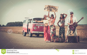 Multi-ethnic hippie hitchhikers with guitar and luggage on a road.
