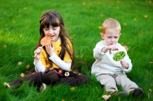 2774631-255371-funny-little-boy-and-girl-eating-big-lollipops-on-a ...
