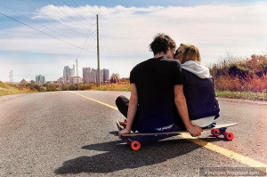 Kissing couple on skate board road young love
