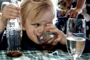 File photo of a young child drinking coca-cola from a glass, coke ...
