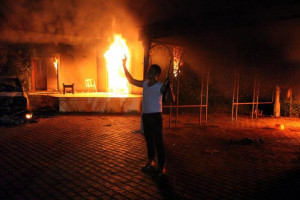 An armed man stands near the burning U.S. special mission in Benghazi ...