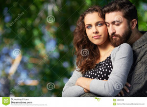 Image of affectionate men embracing his girlfriend while she looking ...