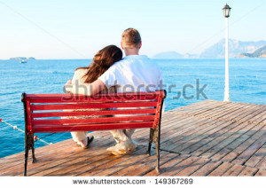 ... -love-couple-sitting-on-a-bench-by-the-sea-embracing-149367269.jpg