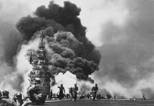 Flames leap from the deck of the USS Bunker Hill, after it was hit by ...