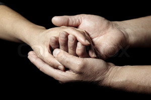 ... 'Hands of senior people supporting each other on a black background