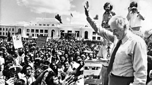 Gough Whitlam is surrounded by supporters the day after his government ...