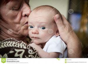 Grandmother loving her cute newborn baby grandchild.