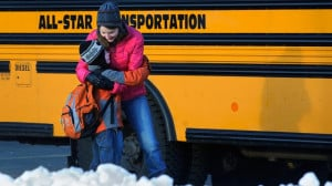 PHOTO: A woman hugs a child before he boards a bus on the first day of ...