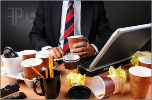 Closeup view of a very cluttered businessmans desk. Man is holding a ...