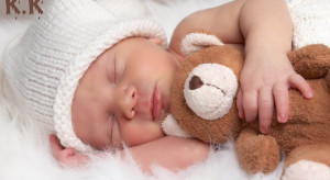 Sleeping newborn baby hugging teddy bear