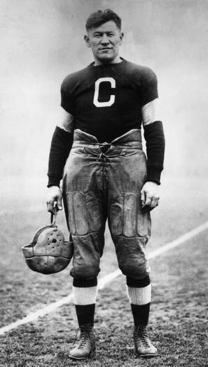 ... American athlete Jim Thorpe posing in a football uniform on a field