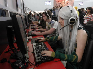 girl dressed in costume plays a video game at the PAX East gaming ...