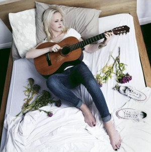 Laura Marling barefoot in bed with her guitar