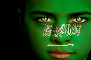 Portrait of a boy with the flag of Saudi Arabia painted on his face