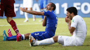 Uruguay's Luis Suarez (R) reacts after clashing with Italy's Giorgio ...