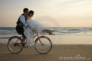 Bride rides the handle bars of a bicycle being driven by her groom on ...