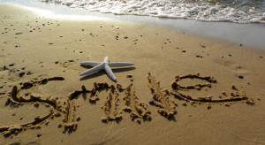 Smile written in the sand and starfish