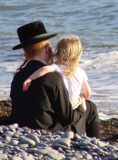 Hasidic Jewish father and daughter at the beach, watching the waves ...