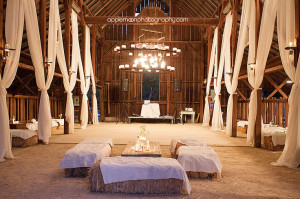 The dance floor, white drapery, and hay bale seating inside the barn ...