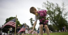 Alex Teeter, 8, places flowers on the grave sites of Battle of ...
