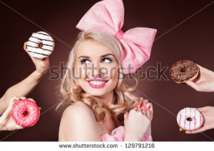 Donuts. Funny woman eating donuts smiling in studio - stock photo