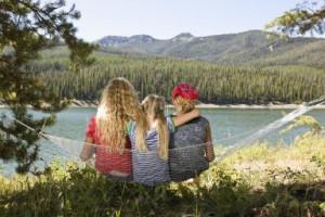 Sister sitting on hammock together by lake - Darrin Klimek/Digital ...
