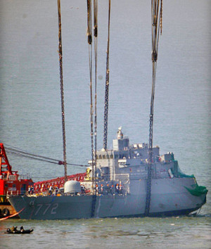 The bow of the sunken South Korean naval vessel Cheonan is lifted by a ...