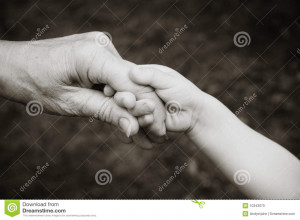 Grandparent holding hands with grandchild in black and white.