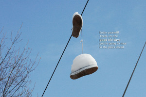 sneaker hanging from power lines, blue sky with a quote: