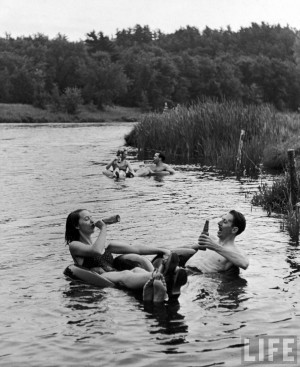 Alfred Eisenstaedt: Couple drinking beer at inner tube floating party ...