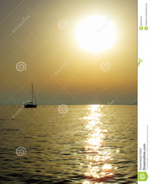 Ship sailing into sunset on the sea. Romantic evening scenery.