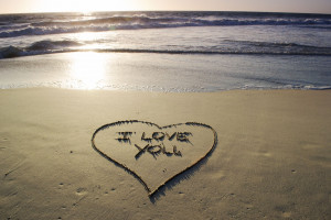 Big heart and I love you written in sand
