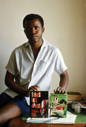 young Chinua Achebe holding the first 2 Editions of his book Things ...