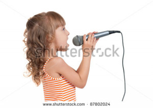 little girl singing with a microphone isolated on white background ...