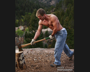 Sexy shirtless male lumberjack chopping wood in the Colorado mountains