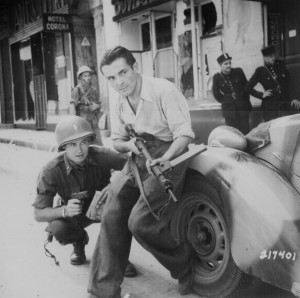 Pictured here are an American officer and a French partisan crouching ...
