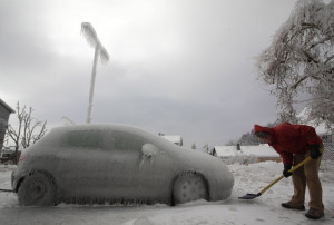 ... man shovels ice next to ice-covered car in Postojna February 3, 2014