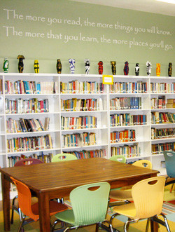 An inspirational wall decal in the library room with books in the ...