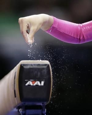 ... Liukin sprinkles chalk on the balance beam at the gymnastics trials