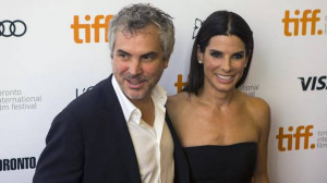 Alfonso Cuaron and Sandra Bullock pose for a photograph on the red ...