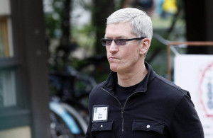 Tim Cook, Apple CEO walks past a news conference being held by Eric ...