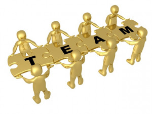 Team Of 8 Gold People Holding Up Connected Pieces To A Colorful Puzzle ...